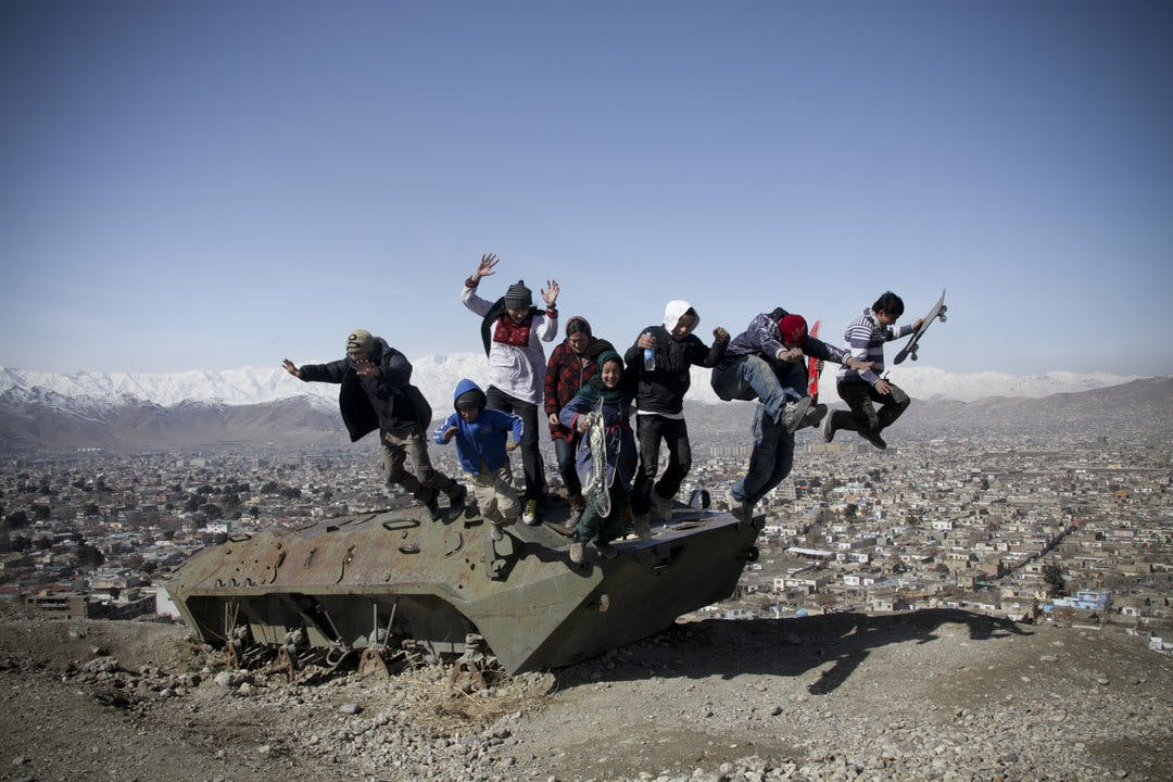 Skatistan Children skateing and jumping of an old destroyed tank